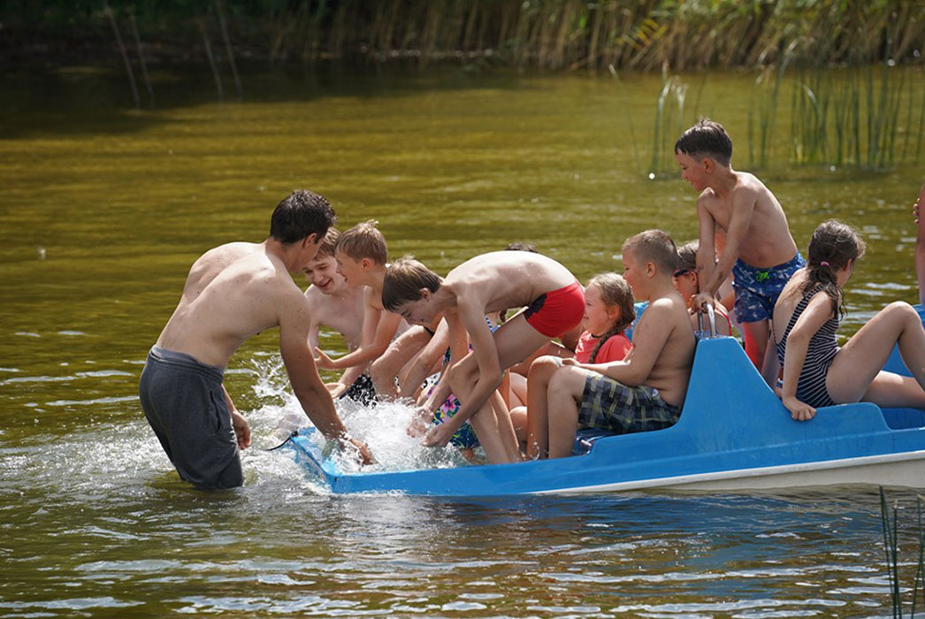 Boys and girls in a boat, laughing, splashing water.