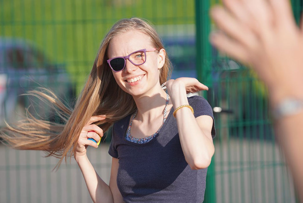 Girl in the sun wearing patch glasses so her left eye can see. Long hair blowing in the wind, and big smile